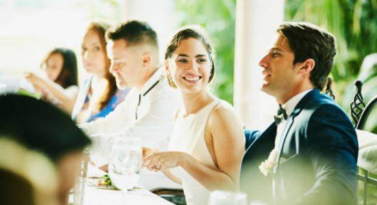Couple de jeunes mariés pendant leur repas de mariage avec leurs convives