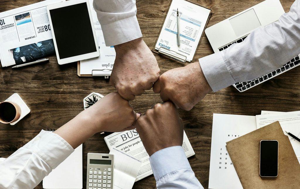 quatre personnes joignent leur poing au dessus d'un bureau avec journaux papiers tablette calculatrice téléphone ordinateur portable