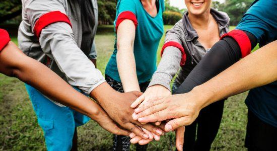 personnes formant une équipe avec des brassards rouges joignant les mains