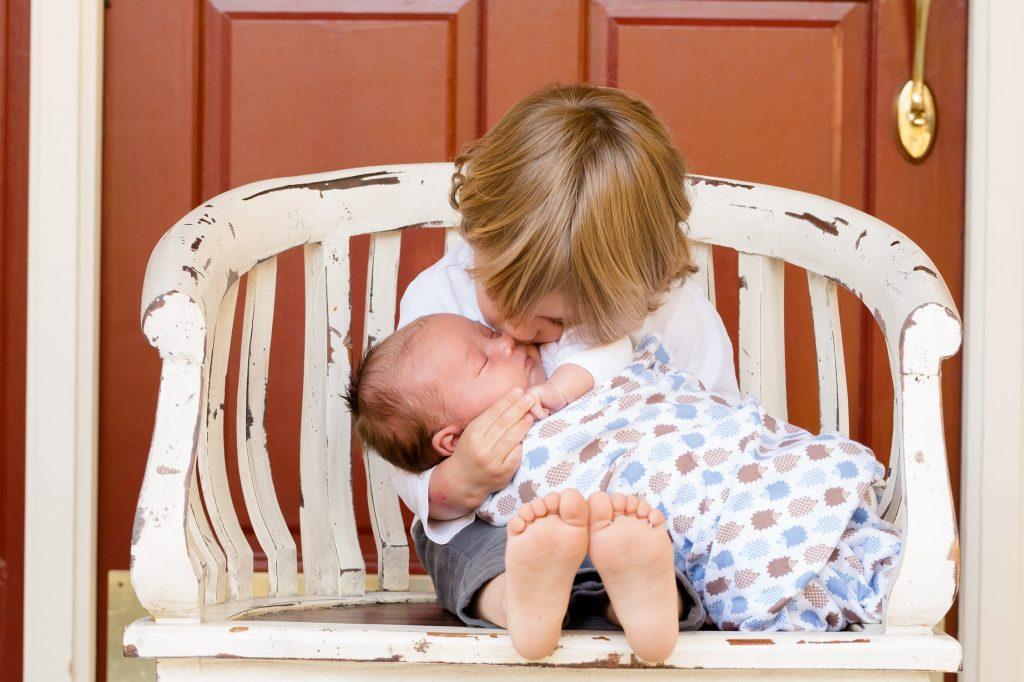Grand frère qui fait un bisou à son petit frère