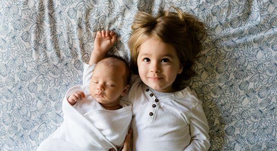 Bébé allongé à côté de son grand frère