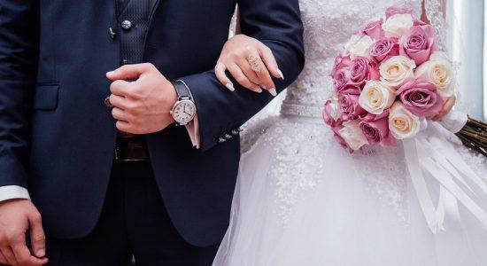 Une femme accrochée au bras de son mari le jour de leur mariage