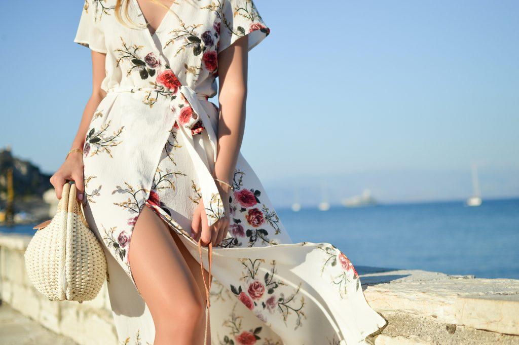 femme potant une robe longue portefeuille blanche à fleurs et un sac paniers blanc